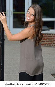 Beautiful young brunette female posing in white high heels, blouse, and black leather pants - next to cast iron fence door