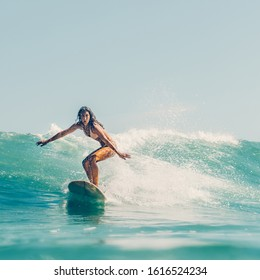 Beautiful young brunette girl in a bikini swimsuit ride wave. Sporty surfer woman surfing in Mauritius in the Indian Ocean on the background of blue sky, clouds and transparent waves. Outdoor Active.