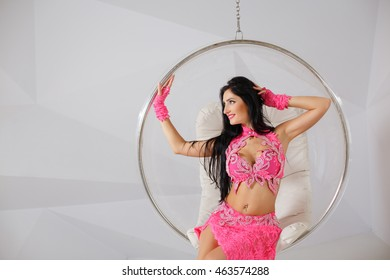 Beautiful young brunette girl with long dark hair in bellydance costume. Attractive girl posing in studio with belly-button piercing. Lying and rests in a transparent glass hair  against a white wall