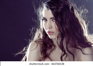 Beautiful young brunette girl with long wavy hair. Curly hairstyle.