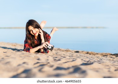 Beautiful young brunette girl lying on the sand on the beach with a camera and smiling.