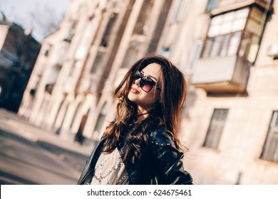 Beautiful young brunette girl on the background of an old wall in the streets of the old town