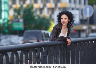 Beautiful young brunette girl on a city bridge.