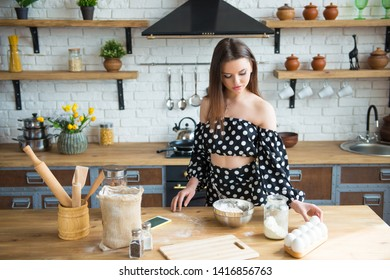 A beautiful young brunette girl in a polka-dot dress kneads a dough and drives in eggs for a cake. Woman cooks in the kitchen according to the recipe