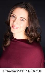 Beautiful young brunette girl studio portrait captured over gray background
