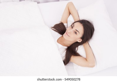 Beautiful young brunette girl waking up and smiling in a white bed.