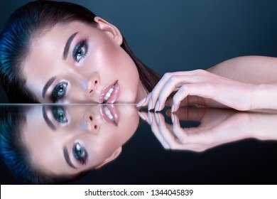 Beautiful young brunette girl wearing evening make up with long lashes and perfect skin posing with mirror at blue background.