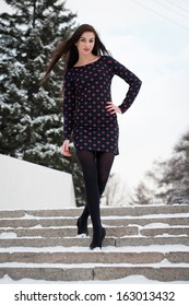 Beautiful young brunette goes down the snow-covered stairs