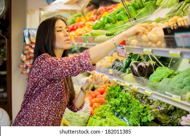 Beautiful young brunette grabbing some potatoes and other vegetables at the supermarket