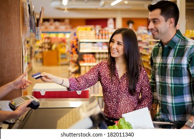 Beautiful young brunette and her boyfriend buying some groceries at the supermarket and paying with a credit card