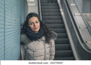 Beautiful young brunette with long curly hair posing in a metro station