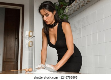 Beautiful young brunette with long hair preparing homemade fresh pasta. Concept of tradition and beauty