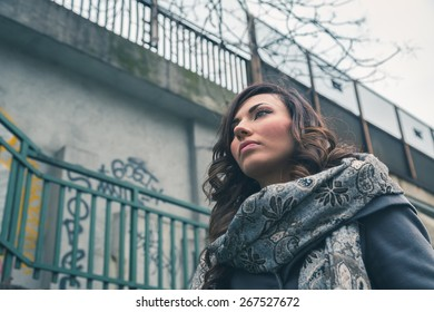 Beautiful young brunette with long hair posing in an urban context