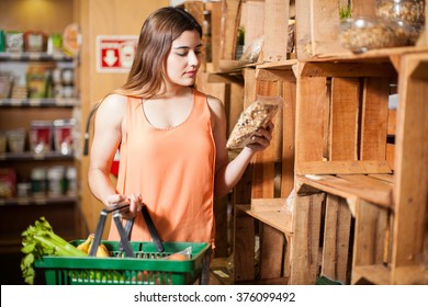 Beautiful young brunette looking at a product label while buying some groceries at the super market
