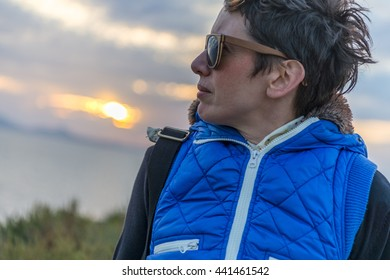 Beautiful young brunette on casual outfit enjoying the amazing sunset in Naxos, Cyclades, Greece.