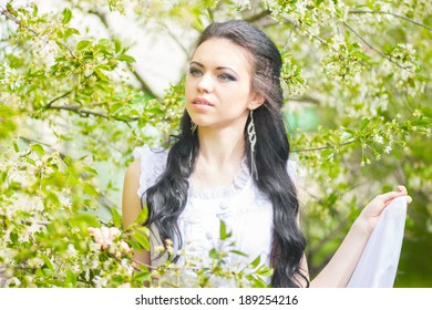 Beautiful young brunette posing in nature. Girl with hair and makeup in white romantic dress