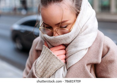 Beautiful young brunette sensual woman are posing on the street in cold winter weather, freezing in scarf and glasses