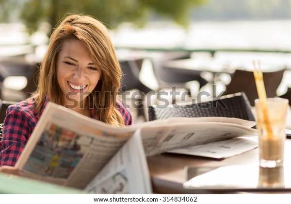Beautiful young brunette sitting in a cafe, drinking coffee and reading newspapers