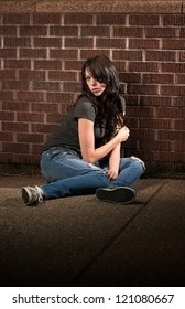 Beautiful young brunette sitting on the floor at night
