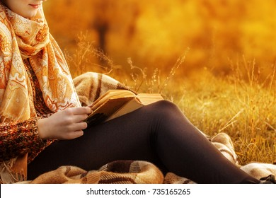 Beautiful young brunette sitting on a fallen autumn leaves in a park, reading a book.woman in a brown sweater sits on a plaid in an autumn park with a book