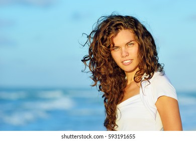 Beautiful young brunette smiling woman with curly hair on the beach of caribbean coastline at sunset