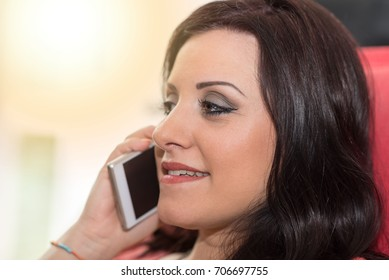 Beautiful young brunette talking on mobil phone at home, light effect