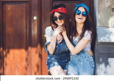 Beautiful young brunette twins sisters, in stylish sunglasses, hugging and laughing. Having fun time together. Wearing denim overalls bright bandanas, posing in front of old doors.