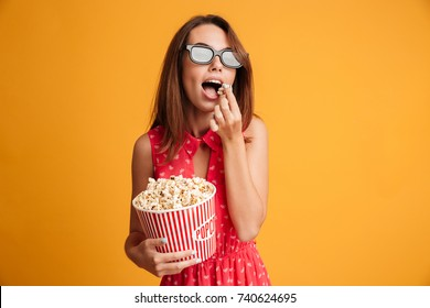 Beautiful young brunette woman in 3d glasses and red dress eating popcorn, looking at camera, isolated on yellow background