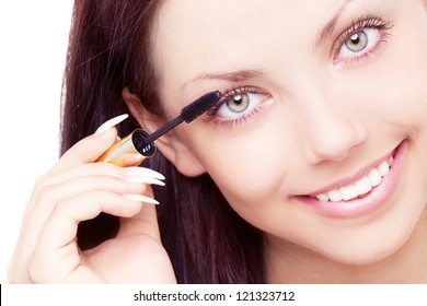 beautiful young brunette woman applying mascara on her eyelashes