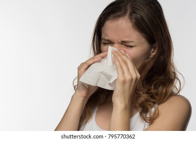 A beautiful young brunette woman becomes ill with a cold and runny nose, sneezes and coughs into a white paper kerchief