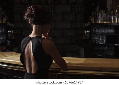beautiful young brunette woman in black dress with glass of red wine in her hand