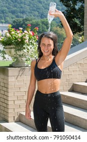 Beautiful young brunette woman in black workout attire outside pours water over head to cool down after excersising