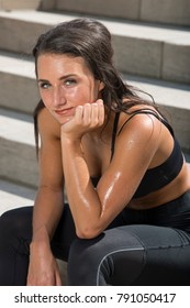 Beautiful young brunette woman in black workout attire outside resting on stairs after exercise with sweat glistening on skin