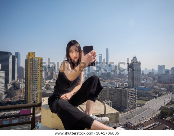 Beautiful young brunette woman in black dress sit on top of mansion roof and take selfie photo with blur Shanghai Bund landmark buildings background. Emotions, people, beauty and lifestyle concept.