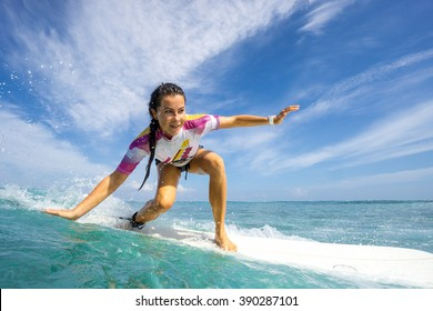 Beautiful young brunette woman in a bright bikini surfing in Mauritius in the Indian Ocean on the background of blue sky, clouds and transparent waves