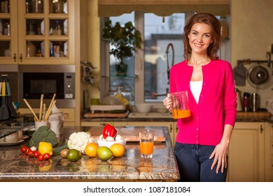 Beautiful young brunette woman in casual outfit cooking in the kitchen in her home. Luxury rich interior