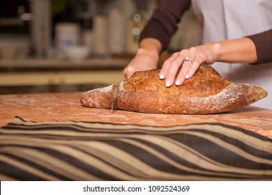 Beautiful young brunette woman in casual outfit cooking in the kitchen in her home, cutting homemade bread. Luxury rich interior