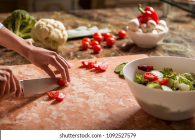 Beautiful young brunette woman in casual outfit cooking in the kitchen in her home, making salad using fresh vegetables (tomato, cucumber, cheese, spices). Luxury rich interior