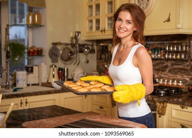 Beautiful young brunette woman in casual outfit cooking in the kitchen in her home, making sweet croissants. Luxury rich interior