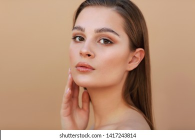 Beautiful Young brunette Woman with Clean Fresh Skin touching own face. Facial treatment. Cosmetology , beauty and spa