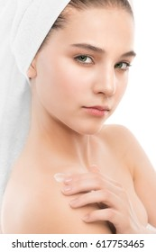Beautiful young brunette woman with clean face and towel on her head applying moisturizer cream on shoulders. Beauty spa model girl perfect fresh clean skin. Youth and skin care concept. Isolated.