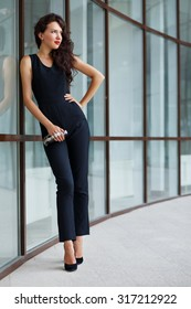 Beautiful young brunette woman with curly hair, wearing black jumpsuit, heeled shoes and clutch bag, posing outdoors near glass office building. Street fashion. Stylish outfit.