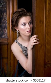 Beautiful young brunette woman dressed in an elegant evening gown looking nervously around a door.