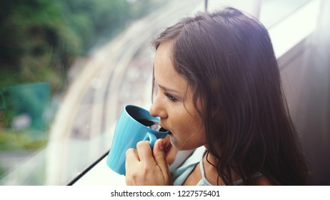 Beautiful young brunette woman drinking coffee by the panoramic window with amazing city view