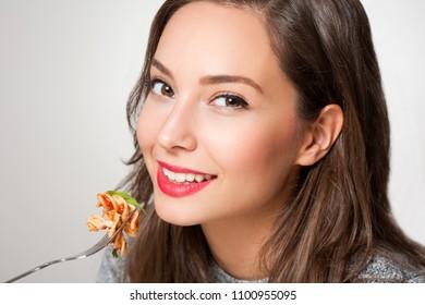 Beautiful young brunette woman eating Italian pasta.