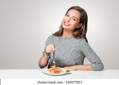 Beautiful young brunette woman eating Italian pasta.