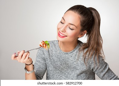 Beautiful young brunette woman eating Italian meal.