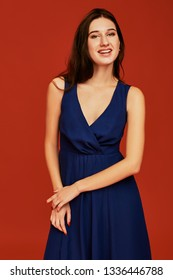 Beautiful young brunette woman in elegant blue cocktail dress with deep decollete is posing for the camera