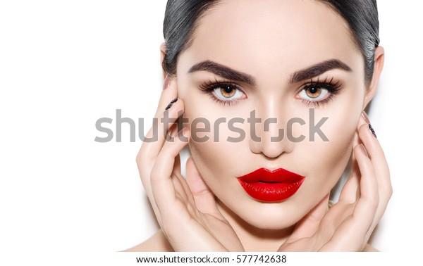 美しい若いブルネットの女性の顔のポートレート。明るい眉、完璧な化粧、赤い唇、顔に触れる美人モデルガール。セクシーな女性がパーティーにメイクを。白い背景に分離型