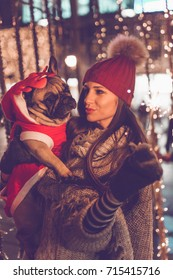 Beautiful young brunette woman with French bulldog enjoying Christmas or New Year night on a city street. Selective focus on dog.